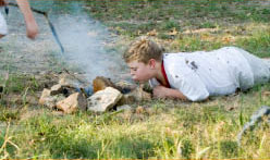 child blowing on campfire wood at campsite