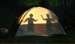 silhoutte of kids in camping tent at campsite