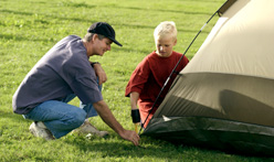 father and son putting up tent