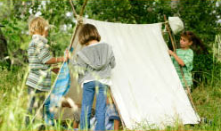 children building small camping tent in meadow