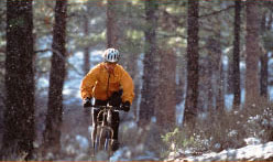 mountain biking in snow in pine forest near campsite