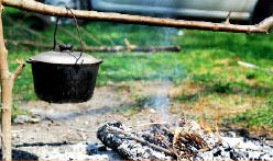camp food showing cooking pot and stick over campfire